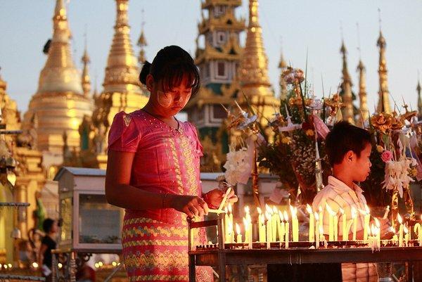 Criança manifestando sua fé na Shwedagon Pagoda em Yangon - Myanmar