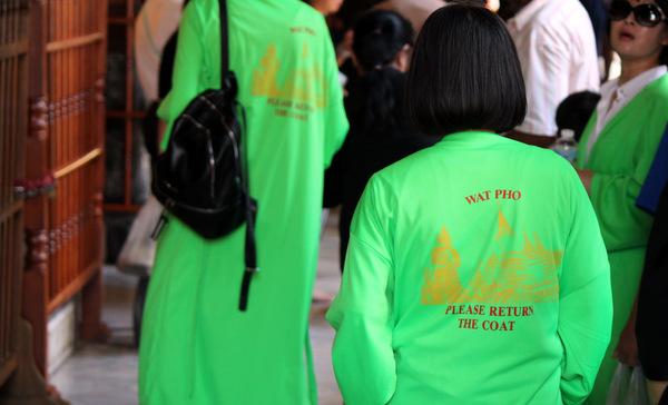 Mulheres utilizando roupas fornecidas aos turistas no Wat Pho para adequarem ao dress code