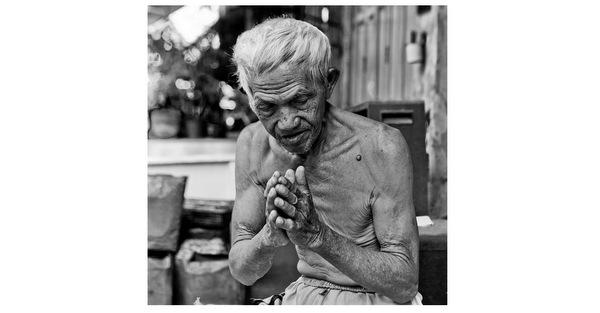 Um homem sentado na rua em Bangkok fazendo um wai, o principal gesto de agradecimento do povo tailandês